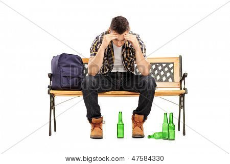 Young man with hangover sitting on a bench, empty beer bottles on the ground, isolated on white background