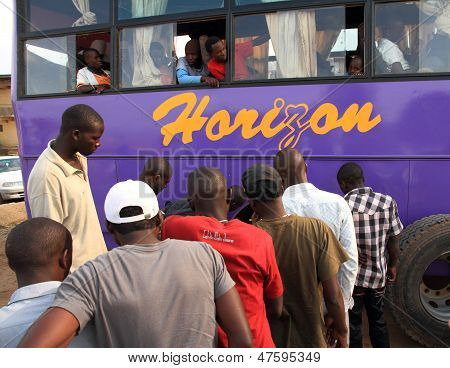 African Bus Passengers Watching The Tire Get Fixed