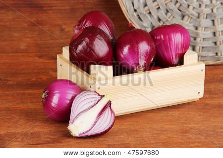 Purple onion in wooden box on wooden background