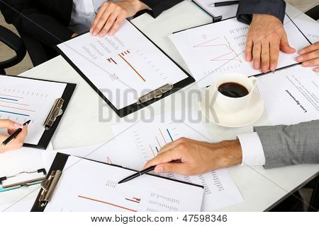 businesspartners hands during discussion of papers close up