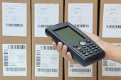 picture of barcode  - Scanning boxes with barcode scanner in working place - JPG