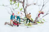 Miniature lumberjacks busy in felling trees