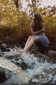 Beautiful woman in fairy forest near a stream