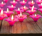 Group Of Burning Candles On Wooden Background.