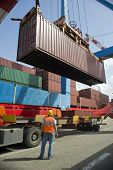 foto of loading dock  - port worker supervising cargo containers uploading at dock - JPG