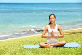 image of relaxing  - Yoga woman meditating woman relaxing by ocean sea doing the Sukhasana - JPG