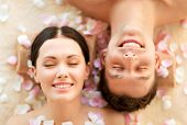 image of cosmetology  - faces of couple in spa salon lying on the massage desks - JPG
