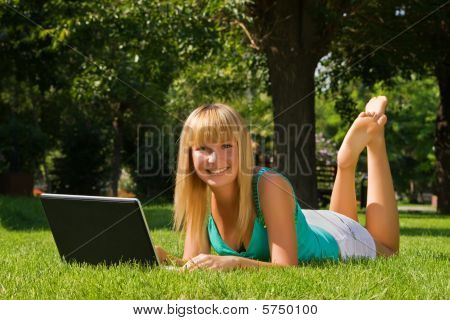 Young Smiling Girl On The Grass With Notebook