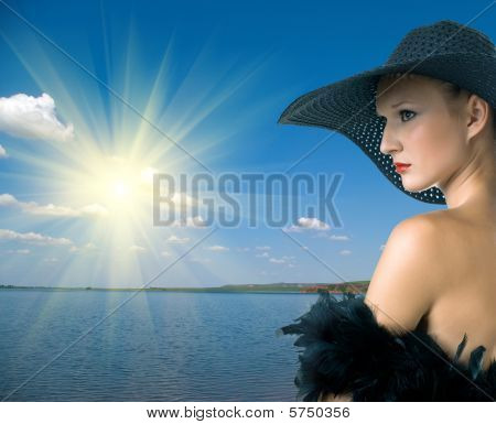 Women In Black Hat And Boa Against Summer Landscape