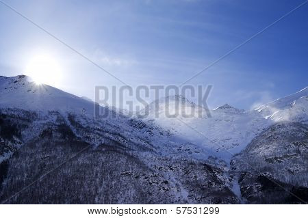 Snowy Mountains In Haze And Sky With Sun, View From Off Piste Slope