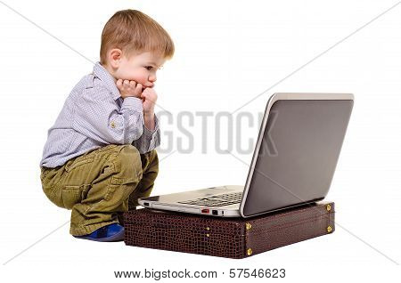 Little boy thoughtfully sits at a laptop