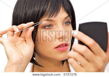 Beautiful Woman Tweezing Her Eyebrows With Tweezers
