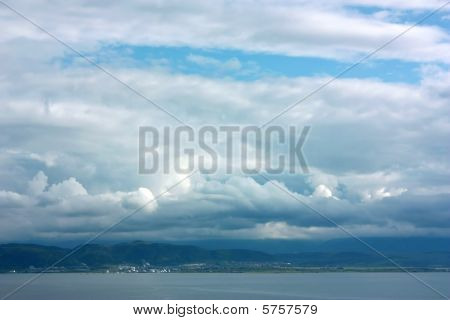 Cloudscape Over Sea And Mountains