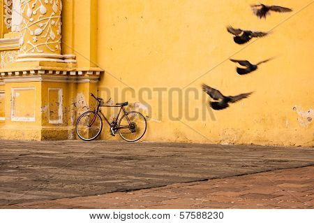 Bicycle Leaning Against Yellow Wall