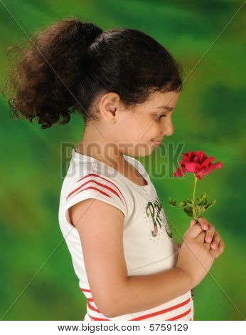 a young pretty girl enjoying the smell of a rose