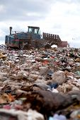 stock photo of trash truck  - View of truck flattening trash in landfill - JPG