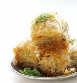 stock photo of baklava  - Turkish arabic dessert baklava with honey and nuts on a silver plate - JPG