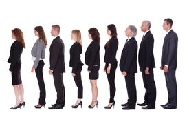 stock photo of lineup  - Long line of diverse professional business people standing in a queue in profile isolated on white - JPG