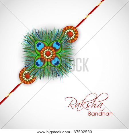 Beautiful rakhi design decorated with peacock feather on grey background on the occasion of Happy Raksha Bandhan.