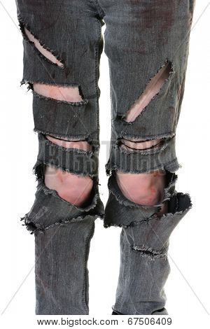 Closeup of a pair of torn and bloody jeans. The female zombie legs have blood smears and cuts. Vertical format over white.
