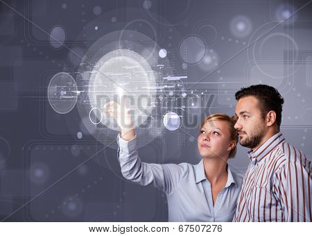 Happy young couple touching abstract high technology circular buttons