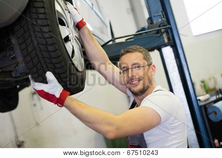 Mechanic checking wheel bearings in a car workshop