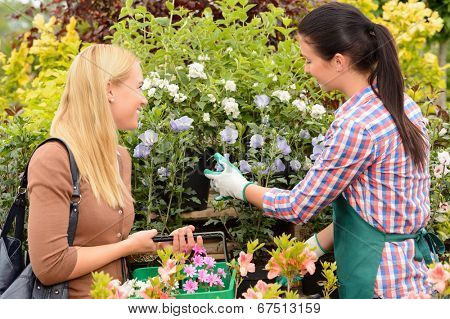 Female florist give advice to customer woman shopping for flowers