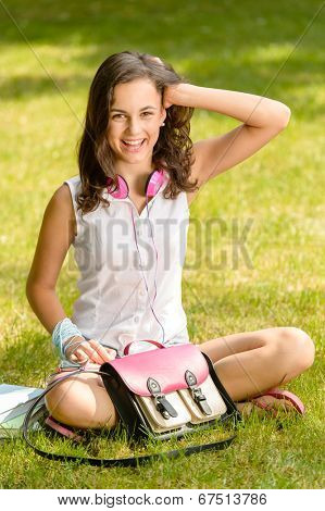 Cheerful student girl with pink satchel sitting on grass summer