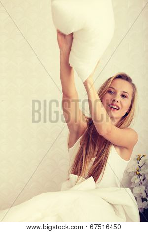 Young happy blond woman ready for pillow fight in the bed