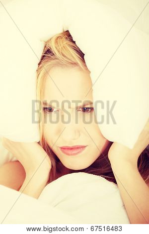 Young caucasian female on bed with pillow on her head. Insomnia concept