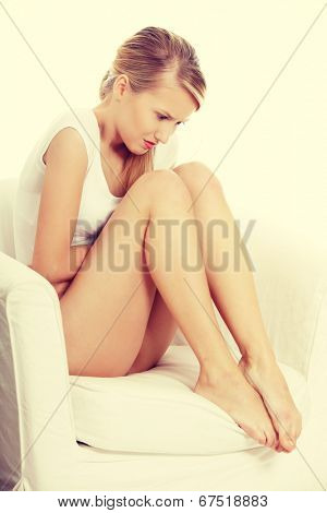 Young blond woman with stomach issues sitting.
