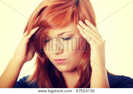 Woman with headache holding her hand to the head.