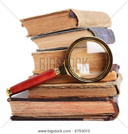 Stack Of Books And Magnifying Glass Isolated On White Background
