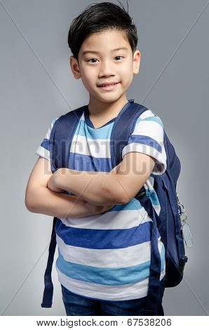 Little Asian Child Standing With A Kit Bag Slung Over His Shoulder