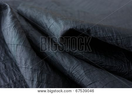 Black fabric or cloth close up. Crinkled textile.