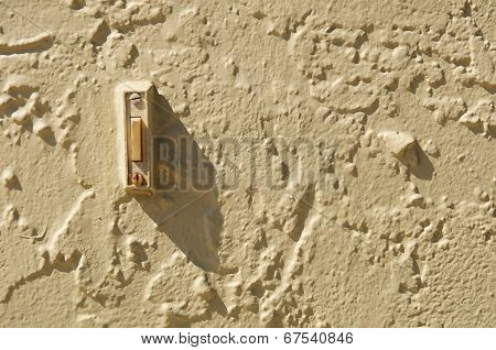 Doorbell In Stuccoed Wall With Shadow And Copy Space