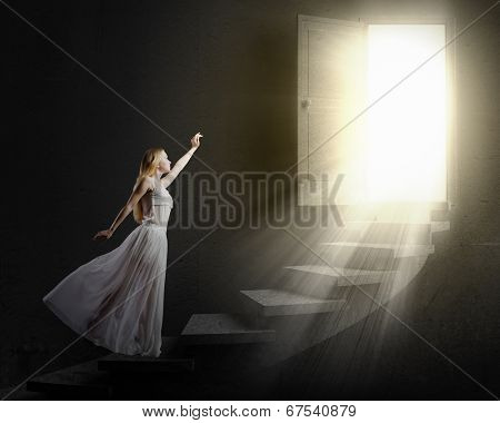 Young woman in white long dress walking up the staircase