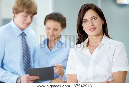 Portrait of beautiful secretary in white shirt looking at camera on the background of co-workers