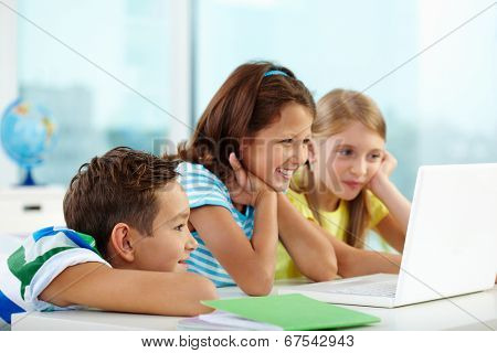 Portrait of curious classmates watching something interesting in laptop