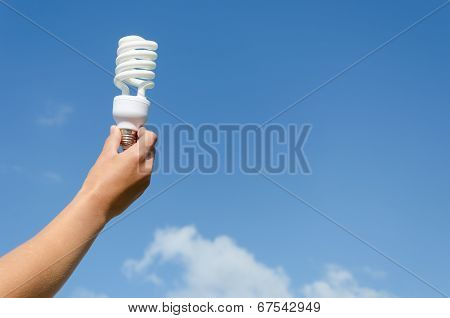 Hand Hold Energy Saving Lamp Blue Sky Background