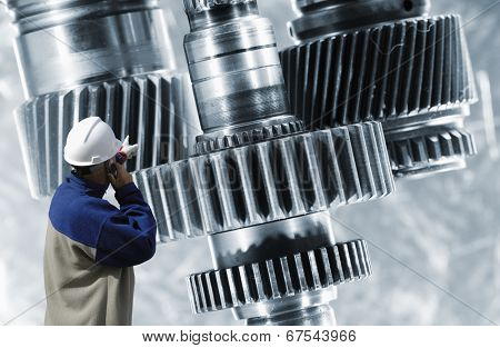 engineer, worker pointing at a large steel and titanium gears machinery