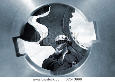 engineer, worker standing inside large gear axle,  engineering and technology concept