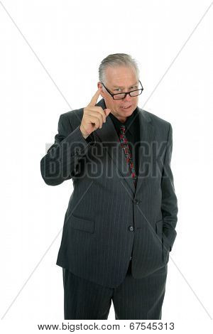 A handsome well dressed fatherly business man looks over his reading glasses and shakes his finger in disapproval at something someone has done or is about to do.  Isolated on white with room text