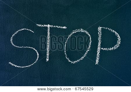 the word stop written with chalk on a chalkboard