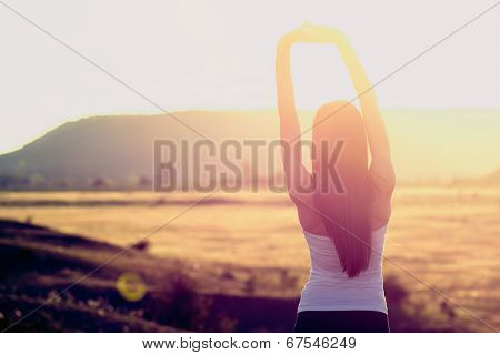 Happy celebrating winning success woman at sunset or sunrise standing elated with arms raised up above her head