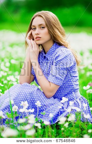 beautiful young woman outdoors, on the meadow with white flowers