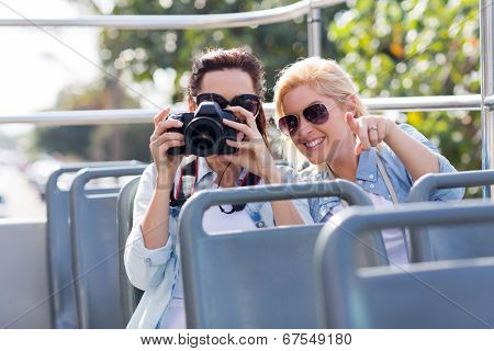 two playful tourists taking fun photos from an open top bus while touring the city