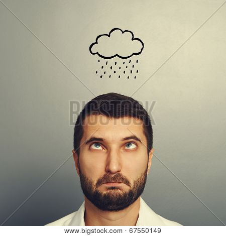 portrait of stressed man with drawing storm cloud over grey background