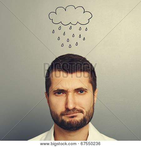 portrait of dissatisfied man with drawing storm cloud over grey background