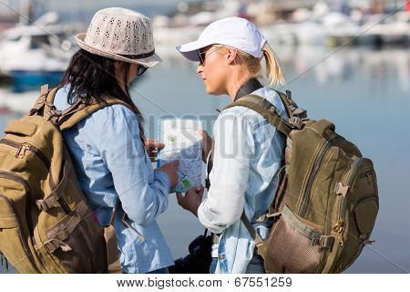 female tourists discussing next visiting stop by the harbor